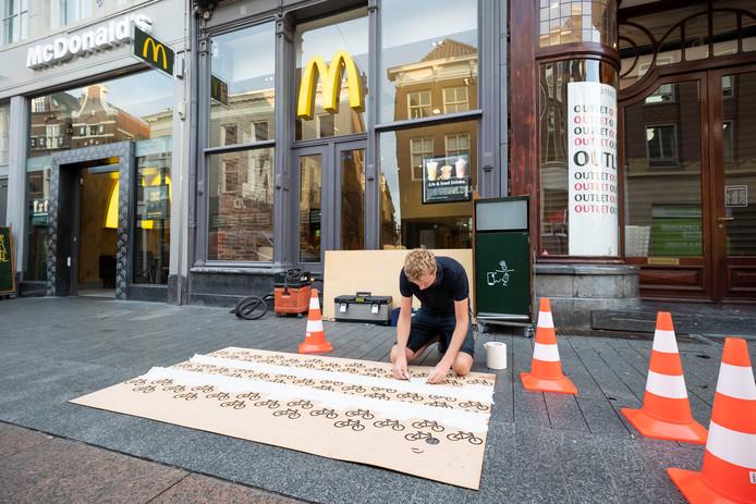 Fier plakt het sjabloon vast waar hij de fietsvakken mee gaat markeren voor de McDonalds aan de Hoge Steenweg.