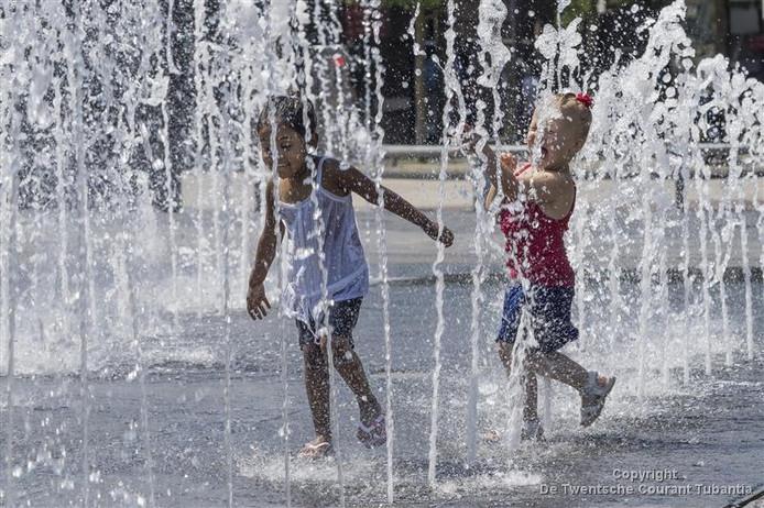 Kinderen zoeken verkoeling op het Van Heekplein in Enschede