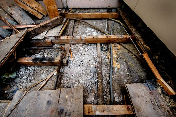 Een lege woning in Amsterdam-Noord waar de loden leidingen in de bodem onder het huis zichtbaar worden, doordat de vloer open is gemaakt.