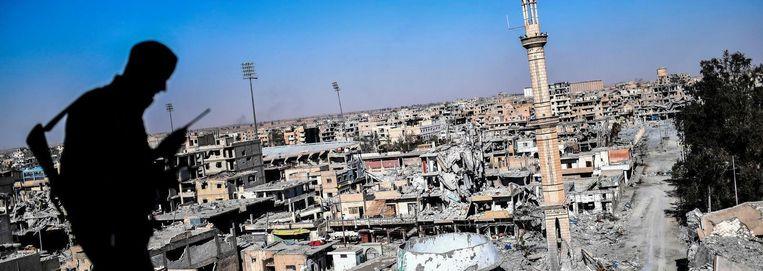 Een lid van de Syrische Democratische Strijdkrachten kijkt uit op Raqqa Beeld afp