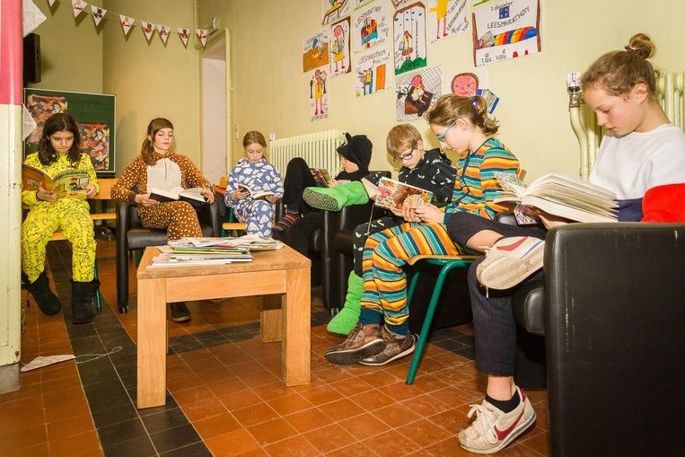 De kinderen, gekleed in hun pyjama, lezen een boek.