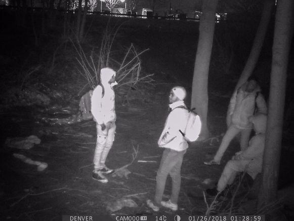 Enkele migranten verschansen zich in een bosje naast de snelwegparking van Groot-Bijgaarden, wachtend op het beste moment om in een oplegger te klimmen.