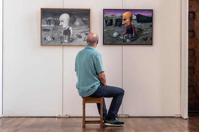 Kunstenaar Sven Hoekstra bij twee versies van De Onderzoeker.