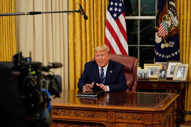 President Donald Trump spreekt de natie toe vanuit het Oval Office. Beeld AP