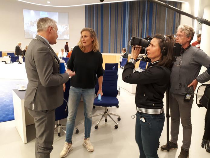 presentatrice Sophie Hilbrand probeert alsnog een vraaggesprek te regelen met burgemeester Arjen Gerritsen, na afloop van de raadsvergadering.