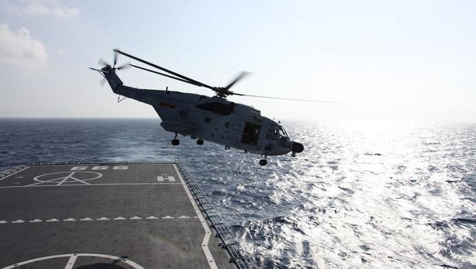 Een helikopter stijgt op vanaf een oorlogschip om de wateren te onderzoeken waar de Boeing verdween