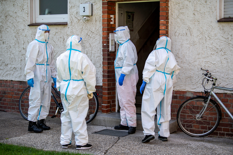 Medewerkers van de Duitse gezondheidsdienst bezoeken werknemers van het vleesverwerkingsbedrijf.  Beeld David Inderlied/dpa