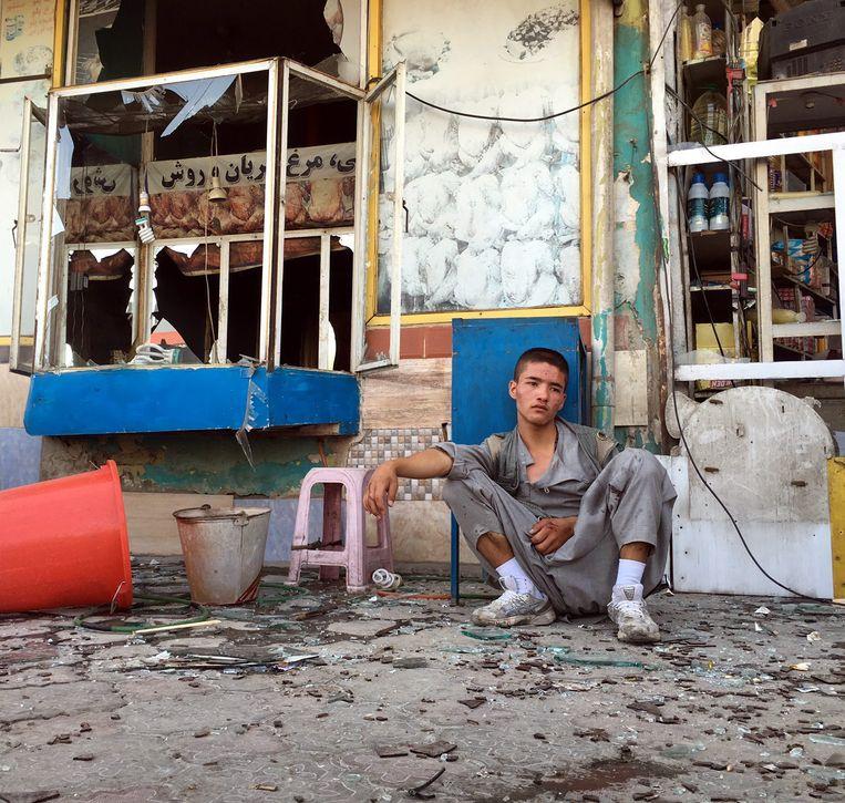 Een Afghaanse jongen in shock na de bloedige zelfmoordaanslag op een demonstratie van de sjiitische Hazara-minderheid in Kaboel, vorig jaar juli. De aanslag was het werk van IS. Beeld EPA