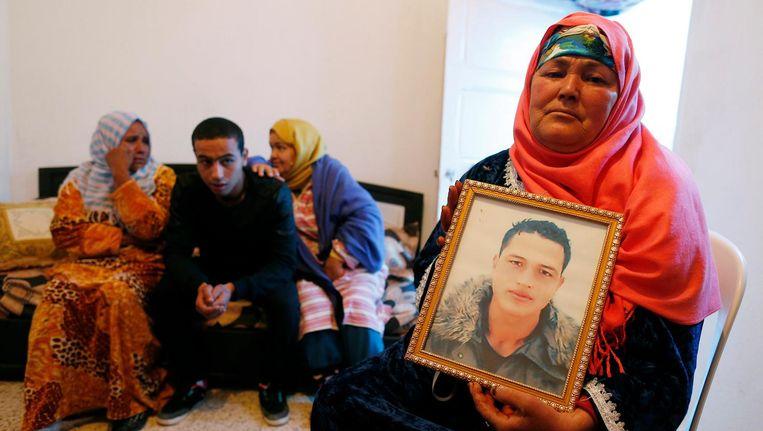 De moeder van de vermoedelijke aanslagpleger toont een portret van haar zoon. Beeld epa