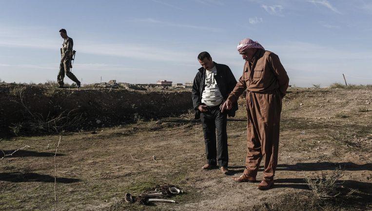 In de buurt van de Iraakse stad Sinjar, een gebied waar veel yezidi's wonen, bekijken onderzoekers menselijke resten. Hier hield Islamitische Staat huis tot peshmerga de stad heroverden. Beeld Sam Tarling