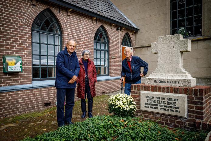 De kinderen Klaas, Anja en Pieter (vlnr) bij het familiegraf met gedenksteen voor hun door de Duitsers doodgeschoten vader