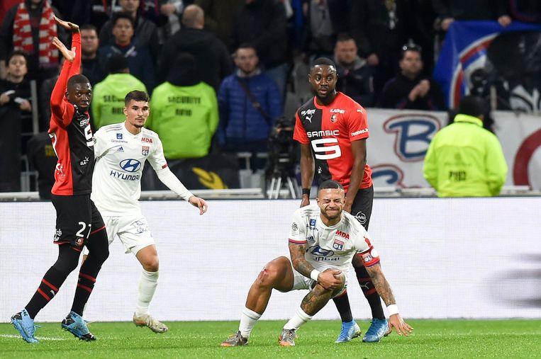 Memphis Depay grijpt naar zijn knie tijdens Lyon - Rennes.  Beeld BSR Agency