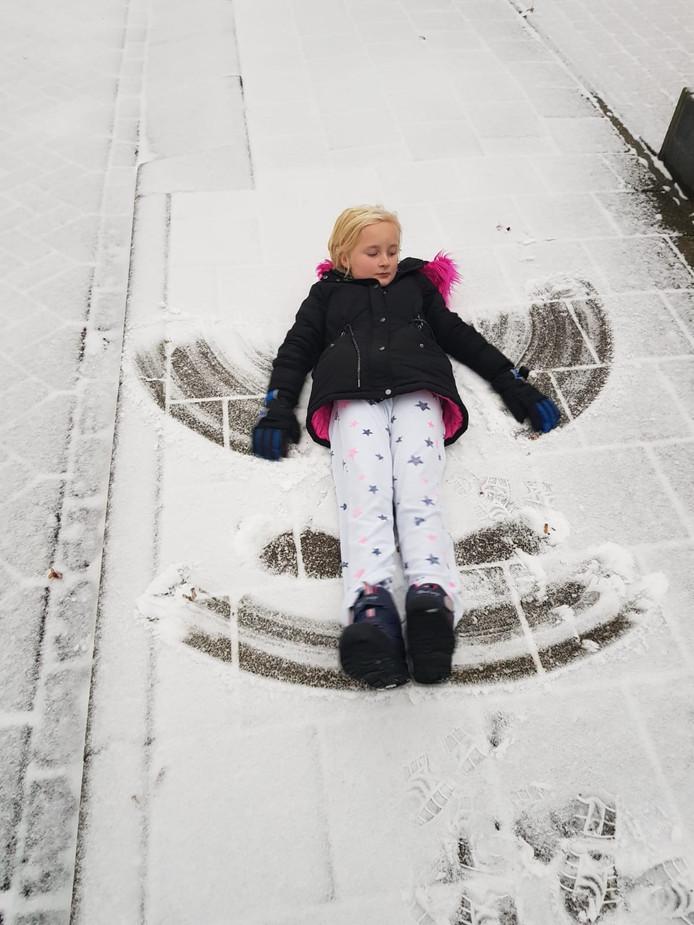 Lotte uit Westervoort maakt een engeltje in de sneeuw