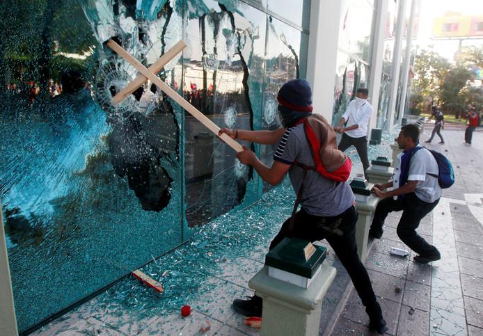 Hondurese demonstranten vernielen de ramen van het Marriott hotel tijdens een protest tegen de herverkiezing van president Juan Orlando Hernandez in Tegucigalpa. Foto Jorge Cabrera