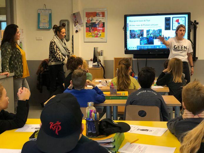 Juf Laura (rechts) geeft de leerlingen van groep 7 instructies over het protest dat zijn gaan schrijven. Links kijken de ouders die invaldocent zijn toe.
