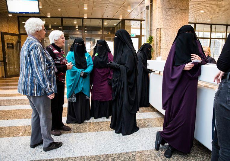 Vrouwen in een nikab in gesprek met twee oudere vrouwen tijdens het debat in de Tweede Kamer over gezichtsbedekkende kleding. Beeld ANP