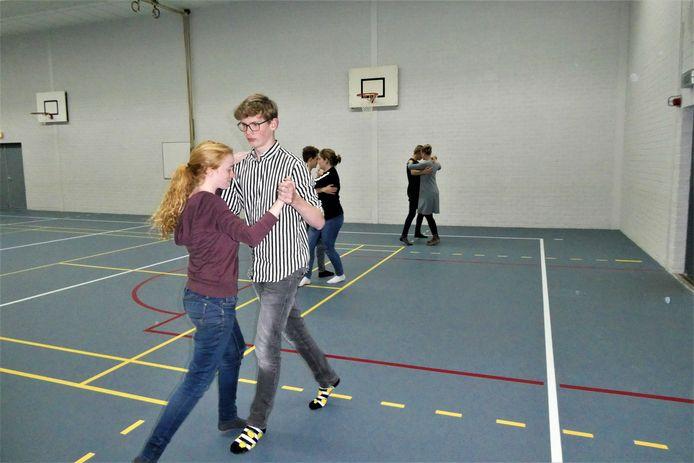 Juliëtte en Gijs dansen met veel plezier de quickstep in de gymzaal van Gymnasium Beekvliet.