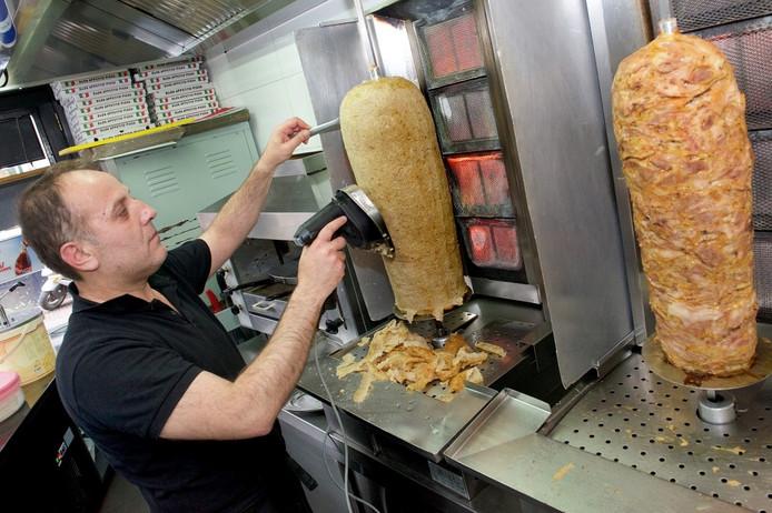 Een medewerker van Kebab Delight in Arnhem snijdt het vlees.