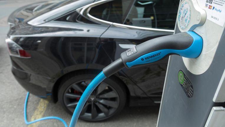 Een auto van Tesla bij een oplaadstation. Beeld epa