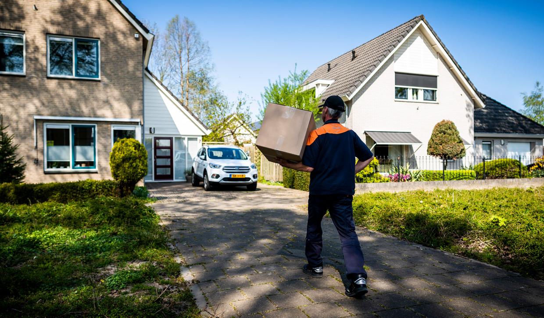 Pakketbezorger Jos brengt pakketjes rond in Duiven.  Beeld Freek van den Bergh / de Volkskrant