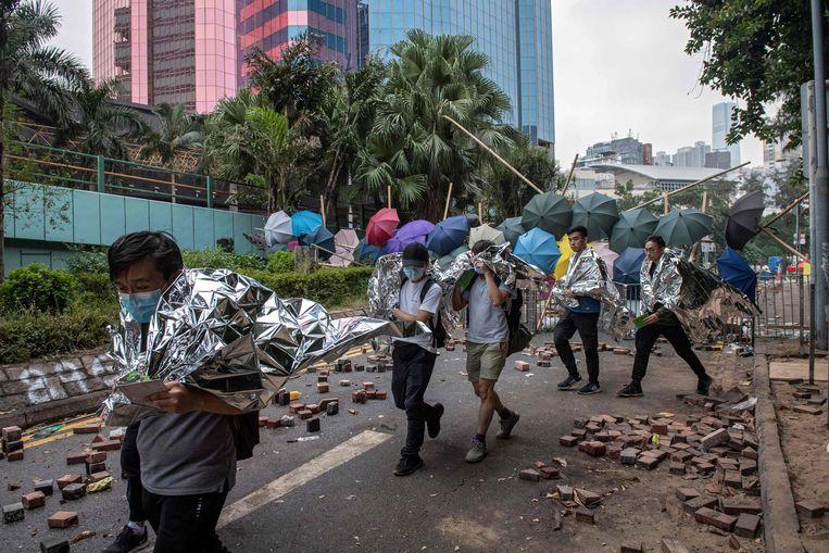 Demonstranten worden uit de universiteit geëscorteerd.