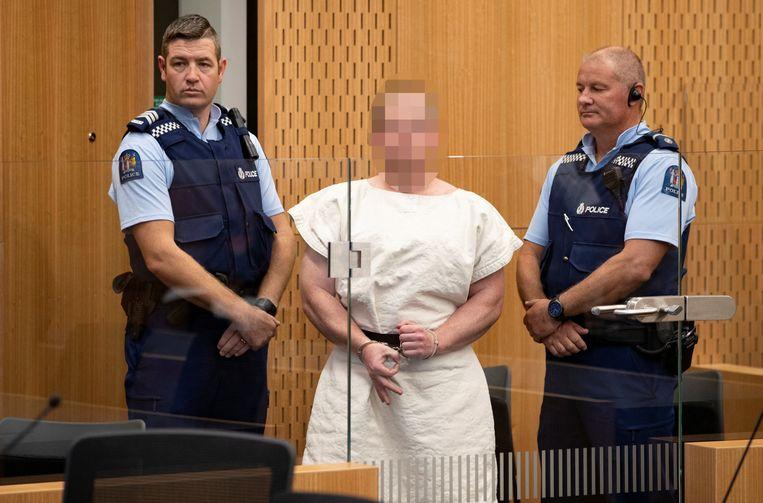 Geëscorteerd door twee Nieuw-Zeelandse politieagenten wordt de verdachte van de aanslagen in Christchurch geboeid de rechtbank binnen gebracht. Beeld REUTERS