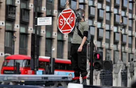 Een gemaskerde demonstrant van Extinction Rebellion is op het dak van een auto geklommen.
