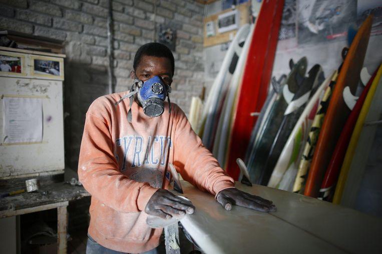 Jokoniah Mawongera uit Zimbabwe is een succesvol bedrijf begonnen in Kaapstad, Zuid-Afrika. Hij repareert surfplanken. Beeld epa