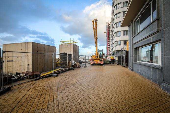 De liftuitgang en de koker met afvoerbuizen voor uitlaatgassen op de zeedijk.