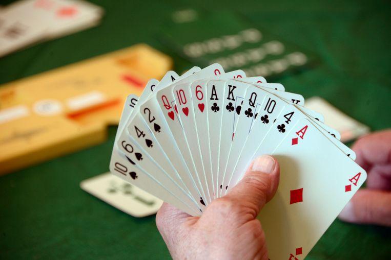 Een gepensioneerde vrouw houdt een waaier kaarten in haar hand. Ze speelt bridge bij een bridgeclub. Beeld Flip Franssen / HH