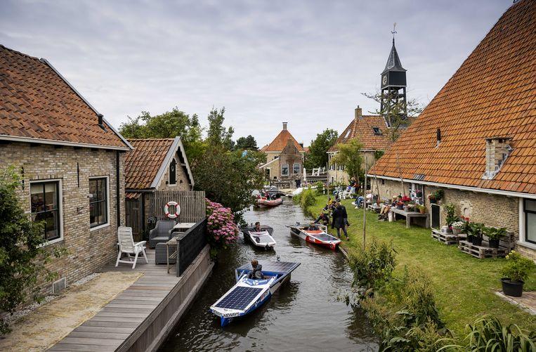 Studenten varen met zonneboten langs alle Friese Elfsteden tijdens de Young Solar Challenge. De 220 kilometer lange tocht moet in vijf dagen volledig op zonne-energie worden afgelegd. Beeld ANP