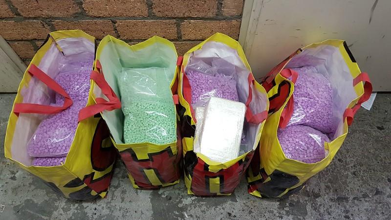 Enkele  tassen vol xtc-pillen, die de politie vond in een van de Tilburgse huizen