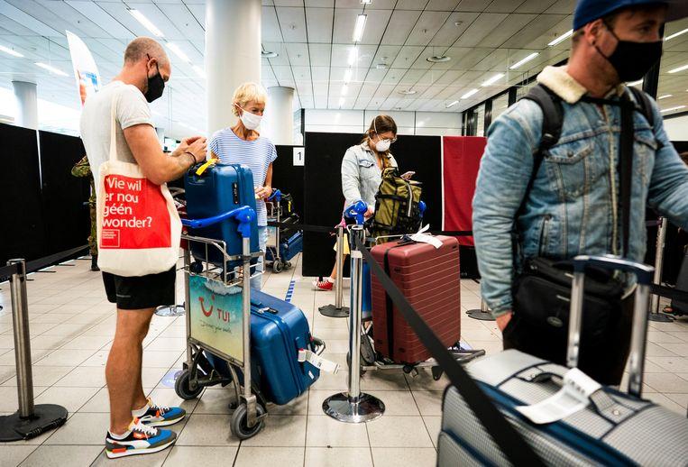 Reizigers staan bij terugkeer in Nederland in de rij voor de coronateststraat op Schiphol.  Beeld Freek van den Bergh / de Volkskrant