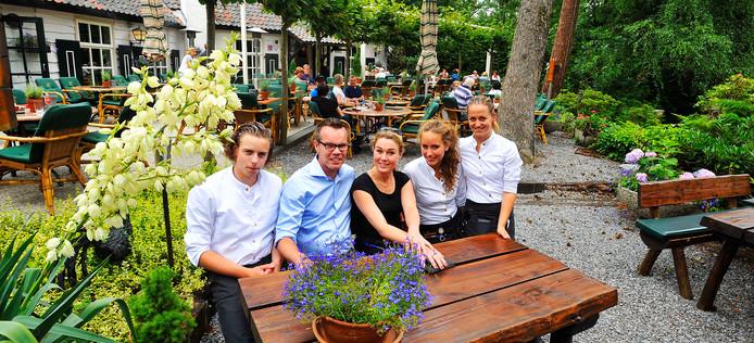 Dick en Laetitia van Ostaden (midden) met ober en serveersters op het terras van Boshuys Hermitage.