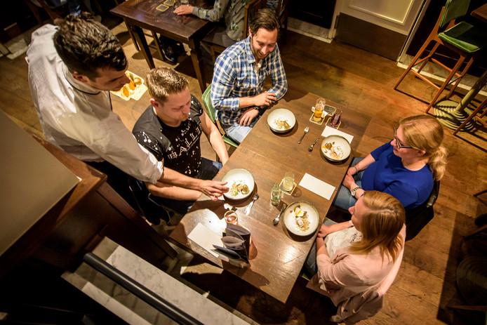 De gasten krijgen een gerecht geserveerd bij Markt 8.