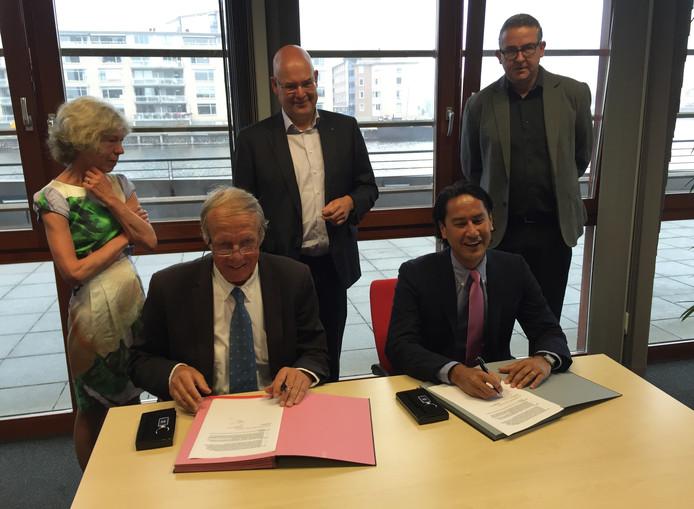 Frans Lievens en burgemeester Harald Bergmann tekenen de contracten. Achter hen mevrouw Lievens, wethouder Chris Simons en Bart Hill van de schouwburg.