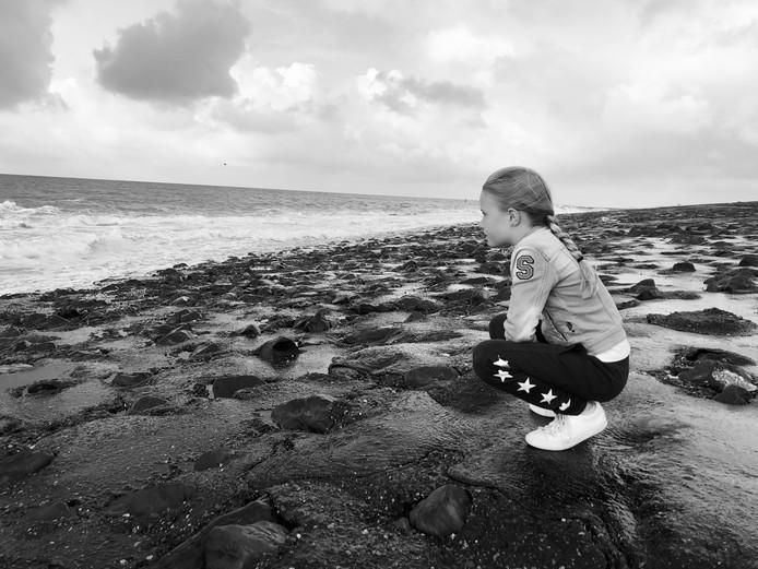 Dochter Sanne geniet van het uitzicht over de zee. Ze is met haar ouders naar het altijd mooie Westkapelle.