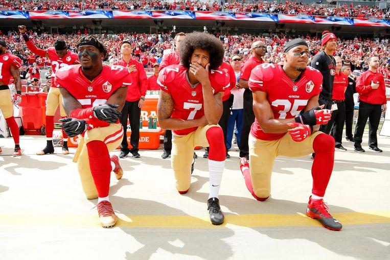 Colin Kaepernick (midden), Eli Harold (links) en Eric Reid (rechts) van de San Francisco 49ers knielen tijdens het volkslied.  Beeld EPA