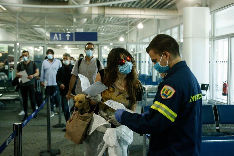 Passagiers schuiven aan voor een coronatest in de Eleftherios Venizelos International Airport in Athene. De Griekse regering stopte dit weekend met de willekeurige screeningstests voor reizigers op basis van hun land van herkomst. Dat had voor verwarring bij toeristen gezorgd.