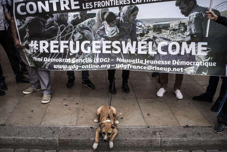 Inwoners in Lyon verwelkomen vluchtelingen met een spandoek. Beeld afp