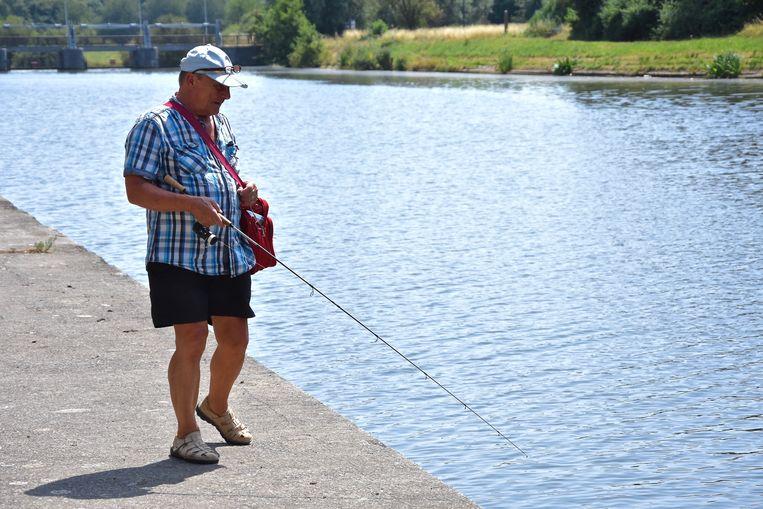 Hittegolf Menen 13u30 - 34°C Deze man probeert hier vis uit de Leie te halen