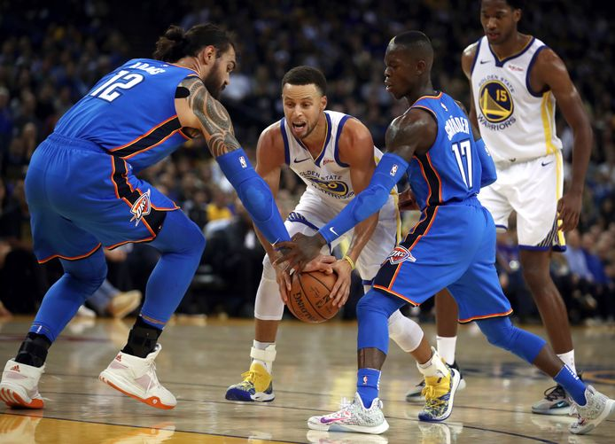 Stephen Curry wringt zich Steven Adams (links) en Dennis Schröder door.