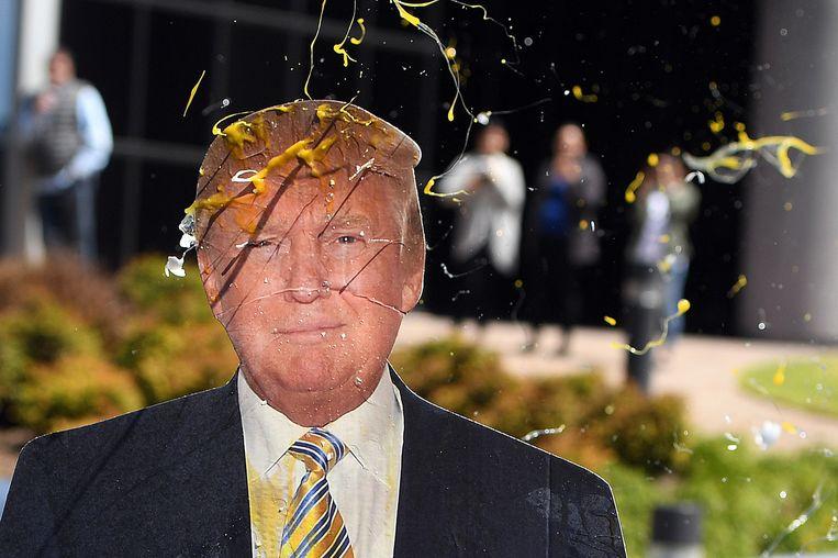 Een bord van Donald Trump wordt met eieren bekogeld. Beeld null