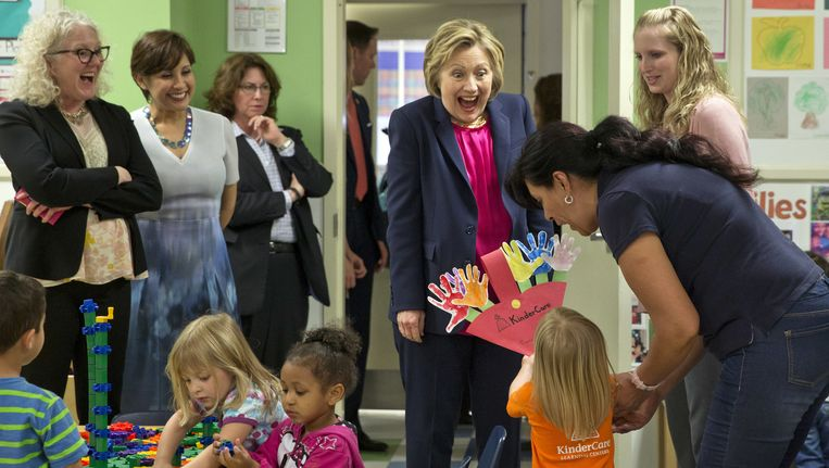 Hillary Clinton krijgt een presentje tijdens een bezoek aan een kinderopvang in Fairfax, Virginia. Beeld ap