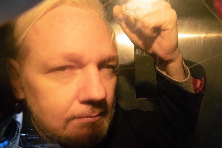 WikiLeaks-oprichter Julian Assange balt zijn vuist als hij aankomt bij de rechtbank in Londen.  Beeld AFP