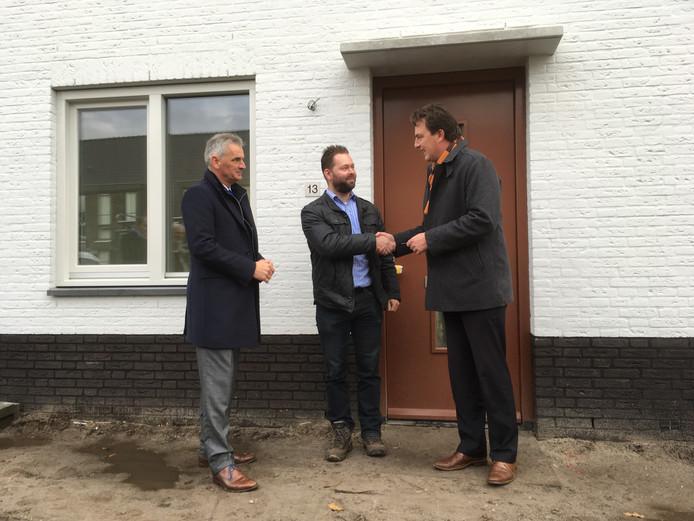 Wethouder Paul de Beer overhandigt de sleutel van de nieuwe energiezuinige woning aan het Wevershof in Prinsenbeek aan toekomstig bewoner Elroy Pluk. Directeur Marcel Hoogendorp van Van Grunsven Ontwikkeling kijkt toe.
