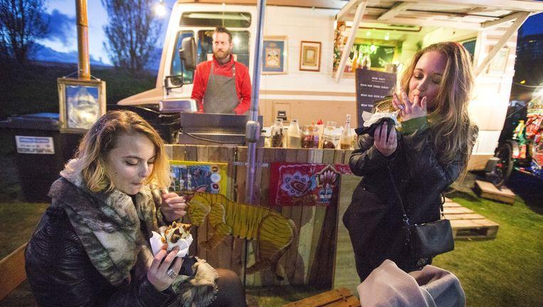 Bezoekers van het foodfestival Rrrollend in Delft genieten van het eten dat wordt klaargemaakt in de trucks. Beeld Najib Nafid