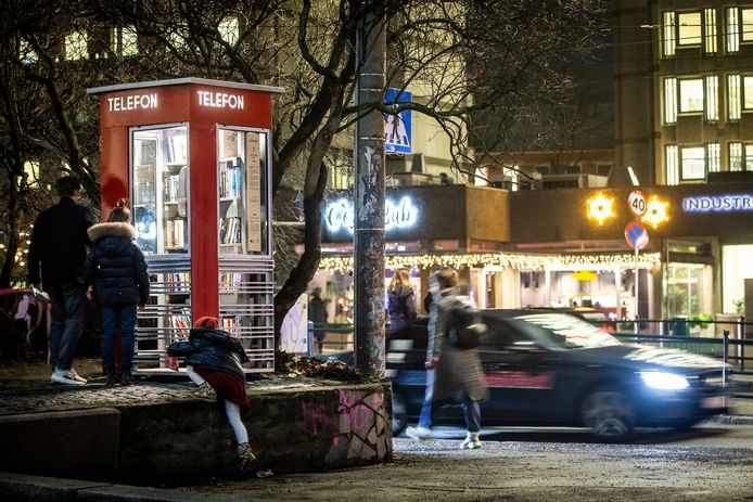 """People walk by a telephone kiosk, the first of 100 protected telephone kiosks in Norway to be converted into a reading kiosk, at Solli plass in Oslo, Friday, Dec. 13, 2019. It has been equipped with shelves and the principle is """"give a book, take a book"""" (Trond Reidar Teigen/NTB scanpix via AP)"""
