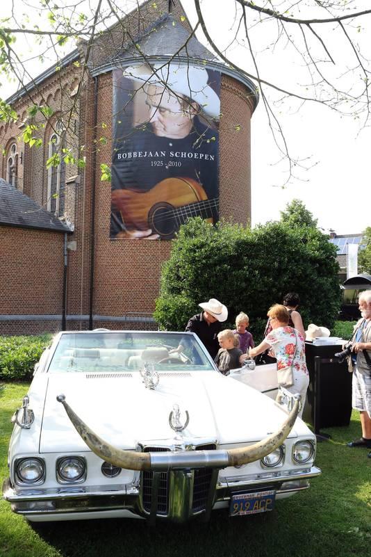 De auto van Bobbejaan aan de kerk met daarop een grote poster van hem.