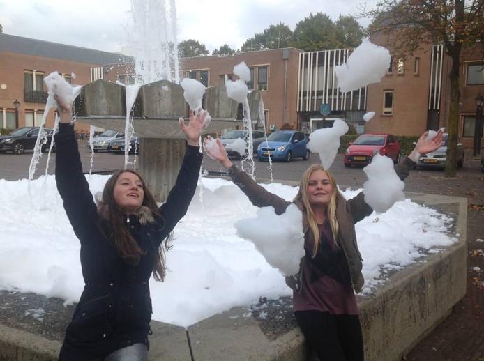 Ilva Overmars (l) en Amy Doppenberg hebben wel schik met het schuim in de fontein.